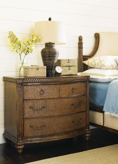 Luxury resort-inspired styling has never been more elegant than in this British West Indies style bachelor's chest. Polynesian influences like woven raffia drawer-fronts and leather-wrapped rattan pilasters enrich this bedside chest for a laid back, tropical appeal. Add storage for clothes, accessories, or linens to your master or guest bedroom with this larger alternative to a nightstand.