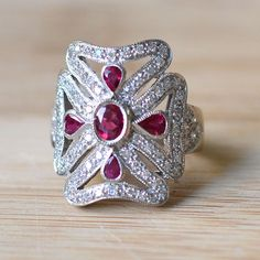 Estate 18K white gold ruby and diamond ring. The ring is set in 18 karat white gold with a center 0.33 carat oval ruby with four pear cut rubies at 0.48 carat total weight and 76 diamonds at 0.76 carat total weight SI1-2 clarity G-H color. Size 7.