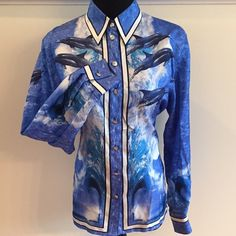 "HOST PICK Dolphin & Waves in Blues 100% Silk Beautiful blues are the background for the dolphin and waves pattern of this 100% Silk blouse. Wave pattern on back. Button down with single button cuffs. Straight hem to wear in or out. Size 38 (converts to US 10), 42"" around bust, 23"" sleeves. Like new, no stains or tears. Escada Tops"