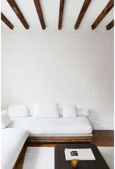 white brick wall, wood beam ceiling, low platform sofa sectional living room