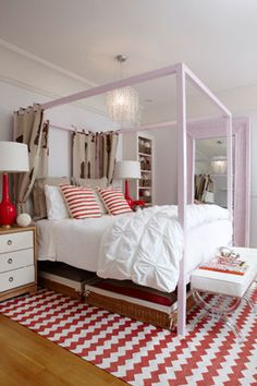 Gauthier Stacy  Sweet pink girl's bedroom with pale cotton candy pink walls two tone white & pink curtains window panels, twin iron canopy beds, pink quilts, pink bolster pillows, Floral Pink & Mother of Pearl Inlay Chest of Drawers, pink duvet & shams and pink birdcage.