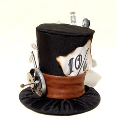 Alice in Wonderland-esque Steampunk Top Hat: I'm thinking I can recreate this with either a redone flea market find or fabric-covered paper party hat, some pretty papercrafts and some clock repair kit pieces (or lift an old clock for a next-to-nothing price). Maybe a couple of cute buttons or other metal accents, too, for a faux-leather band. This is a great one!