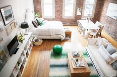A bright loft with exposed brick walls and green accents