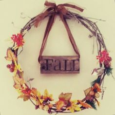 DIY grapevine wreath with stamped wood pallet sign tied on with ribbon.