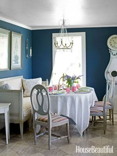 "A custom dark blue creates ""moody drama"" in the breakfast room, used as an intimate dining spot at night."