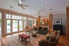 FAMILY ROOM(21X19):THE FAMILY ROOM FEATURES A WALL OF ARTS AND CRAFTS-STYLE CABINETS SURROUNDING AN OVERSIZED FIREPLACE AND TALL CASEMENT WINDOWS WITH VIEWS OF THE TERRACES AND POOL. NOTE CONVENIENT PASS-THROUGH WINDOW FROM WET BAR IN THE KITCHEN.