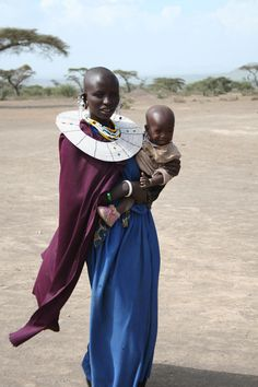 Africa | Portrait of a Maasai mother wearing traditional clothes and beaded necklace, carrying her child, Tanzania #babywearing #beads