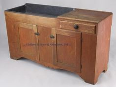 "Sold For $950 PENNSYLVANIA PAINTED PINE DRY SINK, wide metal-lined well beside a single lip-molded drawer, above two fielded panel doors and a cut-out skirt, raised on simple cut-out feet. Old worn red painted surface. Mid 19th century. 33"" H, 19 1/2"" x 60 1/2"". Condition report Good condition with expected wear, patches and loss to rear edge of both ends, proper right door with replaced lock-side rail."
