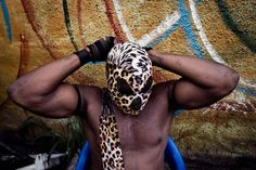 """Six Bolites (Six Punches) takes off his mask after the opening procession to a fetish match. Inspired by American wrestling, each athlete has a """"gimmick,"""" a feature that defines him. Six Bolites head butts his opponents, who then run out of the ring and take shelter in a tree until someone breaks the """"spell."""""""
