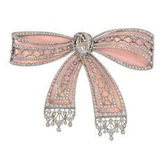 Belle Époque bow brooch, designed in pink enamel with old mine and rose-cut diamond accents, in platinum and 18k yellow gold, the back with elegant foliate patterned engraving in yellow gold, made in France, circa 1910.