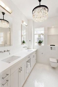 Chic white bathroom glistens from the light of a Restoration Hardware Odeon Glass Fringe Chandelier hung over white hex floor tiles and in front of a white dual washstand accented with nickel pulls, a towel shelf, and a white quartz countertop.