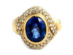 """Ringweite: 52. Gewicht: ca. 10,3 g. GG 750. Signiert """"WOLFERS"""". Feiner Ring mit kornblumenblauem, oval-facettiertem Saphir, ca. 5,4 ct, umrahmt von kleinen..."""