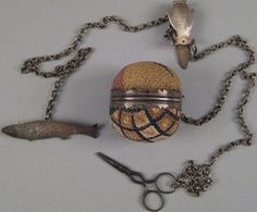 An early 19th century Chester County, Pennsylvania silver chatelaine with needlework pin ball, fish form needle case, hook, and scissors.