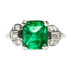 Indian Wells is a classic Art Deco emerald and diamond ring made from platinum featuring a bright green sugarloaf cabochon emerald weighing approximately 2.44cts accompanied with a Guild Laboratories Certificate stating this natural Colombian emerald is medium green in color and moderately included. Indian Wells is flanked by two bezel set diamond baguettes, and enhanced with eight round brilliant cut diamonds with a total combined approximate weight of 0.55ct.