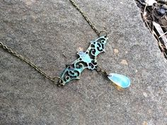 This Listing is for a Antique Bronze, Patina Bat Necklace with a wire wrapped milky Glass Opal Stone dangling at the Bottom. The lenght of this necklace can be customized and it is Nickel and Lead fre