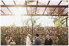 gorgeous handmade garlands with paper flowers and crystals hanging over the altar during the ceremony. By Stacy Reeves