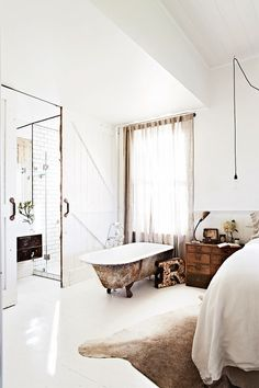 everything! the barn doors, the rusty clawfoot tub in the bedroom, glass shower & library card side table ~ dreamy