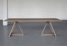 A contemporary trestle table; simple, geometric trestle bases. Thales Table by Brooklyn-based design studio Bellboy. Made in NYC.