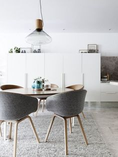 This sleek modern interior is given a soft touch with grey fabric dining chairs and a plush rug.