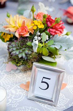 Vibrant floral arrangements placed in metallic vases are stunning against pastel colored table cloths.