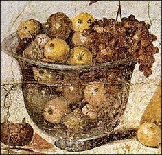 A mosaic still life of a glass bowl full of what could be apples or pears and a bunch of grapes. From the House of Julia Felix, Pompeii, before 79CE.