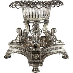 Paul  Storr Silver Centerpiece ca 1820 A truly rare and magnificent sterling silver King George IV period centerpiece displaying Egyptian influence. Four incredibly detailed sphinxes with classic Egyptian headdresses sit with their wings thrust up, each stoically facing outward. Their tails curl and split, meeting in the center to form a lush finial.  A detachable woven basket rests over the wings of the sphinxes.