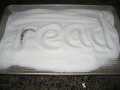 Building literacy in the kitchen activities- using sand or salt in a shallow pan to practice writing letters or words.  Great for tactile learners.  More kitchen literacy ideas at www.growingbookbybook.com.