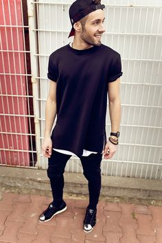 Trendy modern mens fashion. Loose black shirt over black skinny jeans and cap.