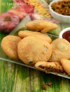 These kachoris probably originated in Jodhpur but are today popular throughout Rajasthan. Very few households actually prepare these crisp, flaky deep fried kachoris stuffed with a onion filling. Steaming hot pyaz ki kachoris or aloo pyaz ki kachoris are sold at most 'namkeen' shops in Rajasthan. Like all kachoris, they are eaten with a sweet and spicy tamarind chutney. You can prepare these kachoris ahead of time and re-heat them in a slow oven just before serving. They are perfect for an…