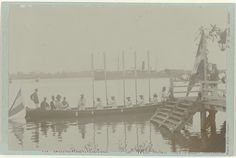 Anonymous | Koninginnedag, Anonymous, 1903 - 1908 | Een boot vaart weg van de steiger. Aan boord Hofstede Crull en zijn vrouw. Hofstede Crull was op dat moment waarnemend gouverneur van Suriname. Koninginnedag te Paramaribo. Onderaan de kaart waar de foto op is geplakt een opschrift.