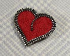 Este broche de cremallera de corazón rojo está hecho de un suéter rojo que encontré en la tienda y luego reducido abajo (fieltro) a través de lavados múltiples. Luego de un plumazo que diseñado hacia fuera y lo rodean con la cremallera! La plata añade un poco de bling y complementa la textura mate del suéter de las lanas. Garantizo que obtendrá comentarios en este broche cada día que usted lo usa, y entonces las personas siempre son sorprendidas al darse cuenta de la cremallera! Super…