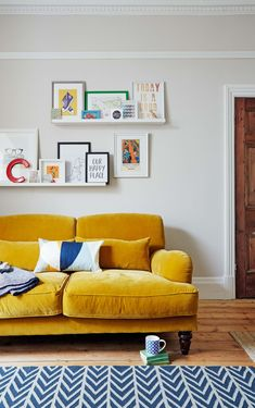 Yellow sofa with artwork on shelves