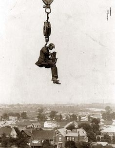 A great image of a really dedicated photographer. This guy had himself hoisted up by a crane to get a shot. Whatever picture he took could not be as interesting as this picture of him taking it! Photograph is from the 1920's