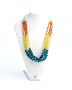Vi Bella Jewelry - Colorblock Necklace - You've seen it for yourself, color blocking is everywhere! The Colorblock Necklace features strand after strand of beads in the season's hottest colors.  Hues of light sea foam blue, bright coral, pale yellow and deep teal blue combine perfectly to create an accessory that really stands out!   Wear with the Colorblock Bracelet and Colorblock Earrings.     Length - 25 - 28 Inches  Handcrafted by Vi Bella Artists in Haiti.  $39.95