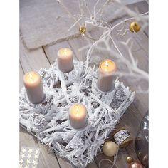 Perfekt als modern interpretierter Adventskranz: eckig geformtes Arrangement mit Zweigen und Zapfen - und mit vier metallenen Kerzenhaltern für Stumpenkerzen