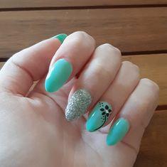 Nail art su base verde,acqua con il decoro di un fiore e glitter argentati