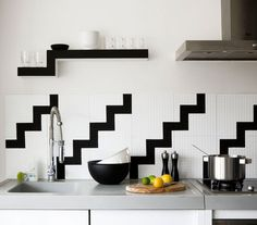You can stick to a monochromatic palette while still adding interest and personality to a room. A continuous pattern, like this modern black-and-white zigzag, running across a counter or backsplash is graphic and unexpected. If you're short on cabinet space, consider hanging floating shelves to hold frequently used tools or display favorite accessories.