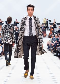 Burberry Spring/Summer 2016. A graphic print silk-wool trench coat, black straight leg trousers and suede tassel loafers