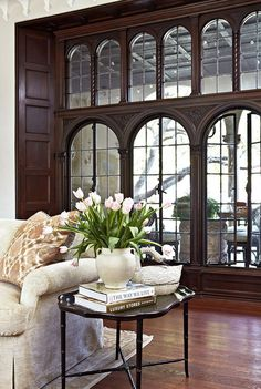Beautiful dark and ornately carved wood casing around leaded-glass windows.