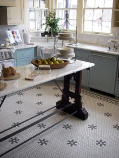 Eye-catching hexagonal tile floor and traditional baker's trestle table as an island- so charming!