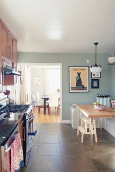 """Generally speaking this kitchen isn't my style, but there are some elements that I really like--paint color, dishtowels, white trim, pillows on the bench.  I'm pinning the pic just in case I ever need to """"Karyn-up"""" a out-of-the-box kitchen.  :-)"""