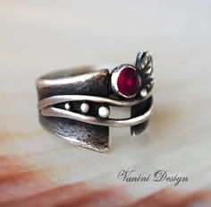 Beautiful ornate Fine silver ring decorated with 5 mm lab created ruby. Has been oxidized to give it a more antique and magical look. 15mm wide, Inside Diameter 18mm US size 7 3/4 International Ring Size Conversion Chart http://www.ringsizes.co Dear customers,If is not a problem for you, I
