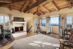 A cabin-like atmosphere encompasses the master bedroom, with vaulted wood ceilings above and plenty of windows and French doors flooding the room with light.