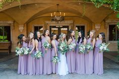 Bride laughing with bridesmaids wearing various lavender floor length dresses   Leslie Ann Photography   Villasiena.cc