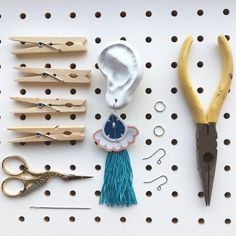 TOOLS FLATLAY - admire the organisation... DIY continues and chaos reigns in my flat, inspiring some uncharacteristically ordered photography. SOMETHING needed to be tidy.  These are the tools and materials used in the construction of my TASSELLED TEXTILE EARRINGS.  The finished earring is displayed on one of the ears that my partner (and HELPER) rudi cut from an old floorboard with his self built CNC machine!  I use clothes pegs to clamp my jewel shapes into place while glue dries, the… Mollie Makes, Clothes Pegs, Textile Jewelry, Recycled Fabric, Cnc Machine, Clamp, Vintage Prints, Statement Earrings, Hand Stitching