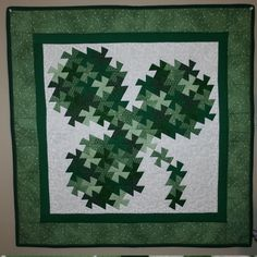 Twisted Shamrock. This Shamrock has had a wee bit of Guinness. Made with multiple greens. Meandering quilt stitch in the background. Backing is light green with white polka dots. 30 x 30 in. Works as a wall hanging or as a table topper. Add a bit of Irish decor to your house. Pattern by Jennifer Watchorn. www.handcraftsbyjennifer.com