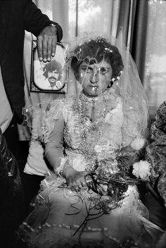 Abbas:   AFGHANISTAN. Kabul. A wedding by proxy: the woman's fiancé, who migrated to Germany, is present in the photograph only. 1992.
