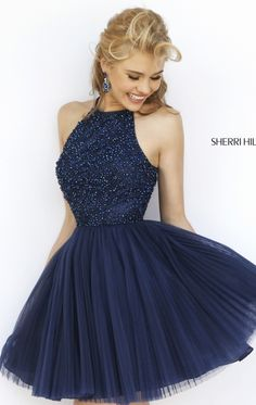 Bring out the beauty in you in Sherri Hill 32335. This cocktail dress features a halter neckline with thin straps leading the keyhole opening at the back. The top is accented with dazzling tonal beads that is sure to make you the center of attention at any event. The solid skirt is overlaid with shirred fabric that flares down onto the mid-thigh finish.