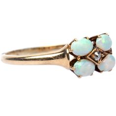 Lovely Victorian Opal Diamond Ring. Kelsey Lake is a lovely Victorian era 14k yellow gold ring that features four pretty oval opals designed in a petal-like motif that display mostly blue and green play of color. The center of Kelsey Lake is touched with old Old Mine Cut diamond guaged at 0.03ct and the shank tapers slightly and is touched with a beautiful antique patina throughout