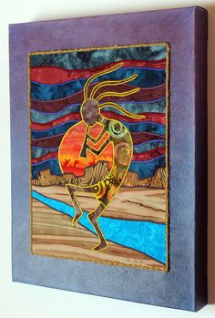 Kokopelli, Native American, Southwest art, Art quilt on canvas, Home decor    Kokopelli is a charismatic figure who is characterized by his dancing and flute playing. He features an elaborate crest on his head and a hunchback which is said to have been where he carried seeds or songs among other things. He is known for bringing great success in hunting, growing crops and human conception.    Kokopellis image was constructed using batik fabrics. When the quilt was finished I sewed along the…